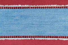 Fond à la mode, jeans et fausses pierres rouges se trouvant sur le satin rouge Photo libre de droits