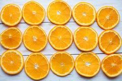 Fond abstrait avec des agrumes des tranches oranges en gros plan sur le fond en bois blanc Photos stock