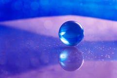 Fond abstrait avec la configuration de bille en verre et d'or (en) Boule sur la table en verre avec la réflexion Images libres de droits