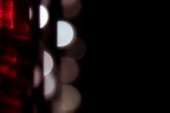 Fond abstrait avec les demi-cercles rougeoyants blancs et rouge sur un fond noir Images stock