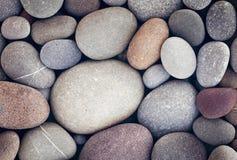 Fond abstrait avec les pierres rondes de caillou dans le rétro montant de vintage plage de pierres lisse Photographie stock