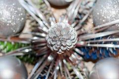 Fond abstrait de Noël L'argent en gros plan a coloré le cône de pin au milieu et l'argent a brouillé des boules autour de lui Photographie stock