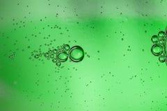Fond abstrait des bulles de l'eau carbonatée par une bouteille en verre verte images stock