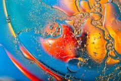 Fond abstrait des gouttes de liquide dans des tons rouges et bleus images libres de droits