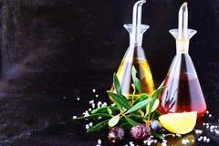 Fond abstrait gris avec les pots en verre d'huile d'olive et de vinaigre de vin avec le citron, le sel de mer, l'ail et la branch Photos libres de droits