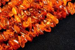 Fond ambre des perles sur le fond noir de tissu Amber Sunstone, un symbole de joie, d'amusement et de bonheur, scintillement de s photos stock