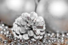 Fond argenté abstrait de Noël Cône de pin coloré par plan rapproché, fil avec des perles et boules brouillées à l'arrière-plan Photos stock