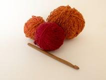 Fond au sujet du tricotage avec les boules oranges et rouges du fil et Image stock