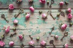 Fond avec de petites roses roses et clés de vintage sur vieil en bois Photographie stock
