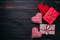Fond avec des boîte-cadeau et des coeurs d'oreiller sur le tabl en bois foncé Photos stock