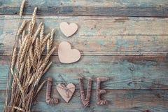 Fond avec des oreilles de blé, des coeurs en bois et d'une inscription Photo libre de droits