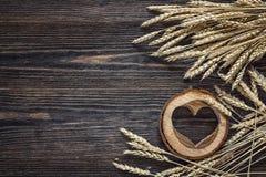 Fond avec des oreilles de blé et des coeurs en bois sur b en bois foncé Photographie stock