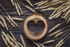 Fond avec des oreilles de blé et des coeurs en bois sur b en bois foncé Photos libres de droits