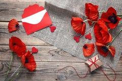 Fond avec des pavots rouges, une enveloppe et le boîte-cadeau sur un rusti Photos stock