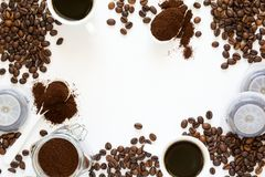 Fond avec du café assorti : tasses d'expresso, de grains de café, de poudre et de capsules sur le fond blanc Photos stock