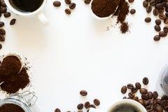 Fond avec du café assorti : tasses d'expresso, de grains de café, de poudre et de capsules sur le fond blanc Image libre de droits