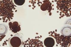 Fond avec du café assorti : tasses d'expresso, de grains de café, de poudre et de capsules sur le fond blanc Image stock