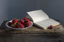 Fond avec la fraise et les livres rouges sur la table Photographie stock libre de droits