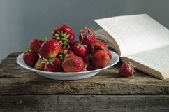 Fond avec la fraise et les livres rouges sur la table Photo libre de droits