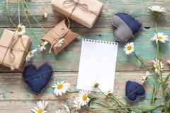 Fond avec la page blanche du bloc-notes, des marguerites et des boîte-cadeau Image stock