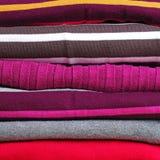 Fond avec la pile d'habillement de tricotage chaud Photographie stock