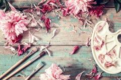 Fond avec la pivoine et les pétales roses, les brosses et la palette sur le Th photographie stock libre de droits
