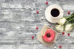 Fond avec la tasse de café, de beignet et de roses blanches sur un gris Images stock