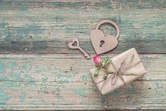 Fond avec le boîte-cadeau, la petite fleur rose, le serrure-coeur et la clé Image libre de droits