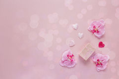 Fond avec le boîte-cadeau, les fleurs d'orchidée et les coeurs sur un Ba rose Photos stock