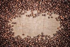 Fond avec le cadre du macro plan rapproché rôti de graines de café sur le contexte de nourriture de toile de jute Photo stock