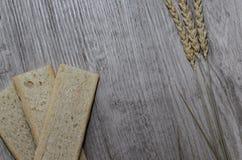 Fond avec le pain croustillant des grains de blé et les oreilles du blé sur un fond en bois Nourriture saine Photographie stock libre de droits