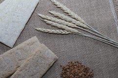 Fond avec le pain croustillant des grains de blé et les oreilles du blé sur un fond en bois Nourriture saine Image stock