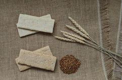 Fond avec le pain croustillant des grains de blé et les oreilles du blé sur un fond en bois Nourriture saine Image libre de droits