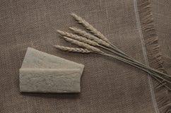 Fond avec le pain croustillant des grains de blé et les oreilles du blé sur un fond en bois Nourriture saine Photographie stock