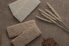 Fond avec le pain croustillant des grains de blé et les oreilles du blé sur un fond en bois Nourriture saine Images libres de droits