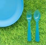 Fond avec le plat bleu et une fourchette et une cuillère sur le g vert Images libres de droits