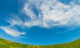 Fond avec le pré et les nuages Photographie stock