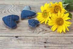 Fond avec les coeurs jaunes de tournesol et de jeans sur vieil en bois Photo libre de droits