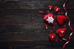 Fond avec les coeurs rouges de tissu et ruban sur vieil en bois foncé Images stock