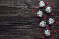 Fond avec les coeurs rouges et vitreux sur la vieille table en bois foncée Photos libres de droits