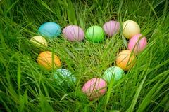 Fond avec les oeufs de pâques colorés sur le pré dans la forme de coeur Photo libre de droits
