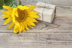 Fond avec les tournesols et le boîte-cadeau jaunes sur le vieux boa en bois Photo libre de droits