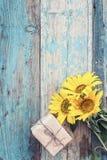 Fond avec les tournesols et le boîte-cadeau jaunes sur le vieux boa en bois Photographie stock libre de droits