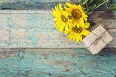 Fond avec les tournesols et le boîte-cadeau sur le vieil esprit de conseils en bois Photos stock