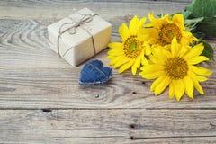 Fond avec les tournesols, le boîte-cadeau et le coeur sur la vieille BO en bois Photo stock