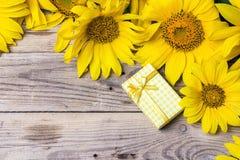 Fond avec un bouquet des tournesols et du boîte-cadeau jaunes sur a Image libre de droits
