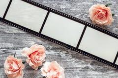 Fond avec un cadre sous forme de film, et roses roses dessus Images stock