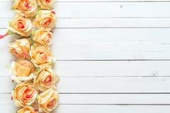 Fond avec une frontière des roses de pêche sur les planches en bois peintes Photo libre de droits