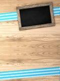 Fond bavarois d'Oktoberfest avec la frontière à carreaux blanc bleu sur le panneau en bois et le tableau noir rustiques, rendu 3d Images stock