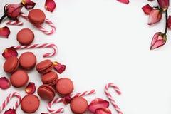 Fond blanc avec des pétales des roses rouges, des macarons et des bâtons de caramel ; Photos libres de droits